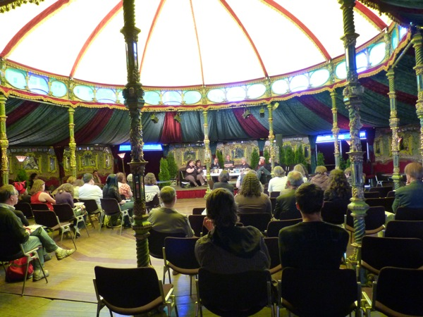People attending a panel under a glowing carousel-y gazebo-like dome tent thing.